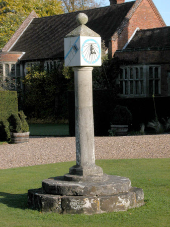 Block sundial painted for hours with metal 'hands', mounted on a stone column, with separate stone ...