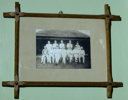 Twelve cricketers outside a thatched pavilion