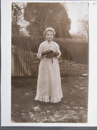 Unknown Village schoolgirl dressed in costumes of a servant cleaning a shoe, Dyrham School, ...
