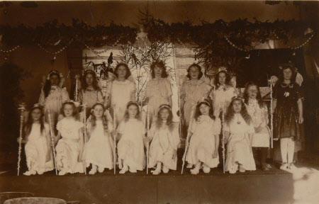 Village school girls dressed in white holding wands, Dyrham School, Gloucestershire