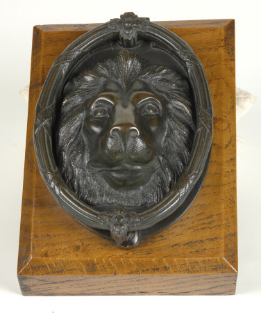 One of a Pair of Bronze Door Knockers formed as Lions masks with bound Wreaths as Handles, with Oak ...