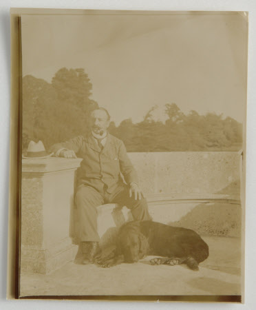 Walter Ralph Bankes (1853-1904) with black labrador, on stone seat, south terrace, Kingston Lacy, ...