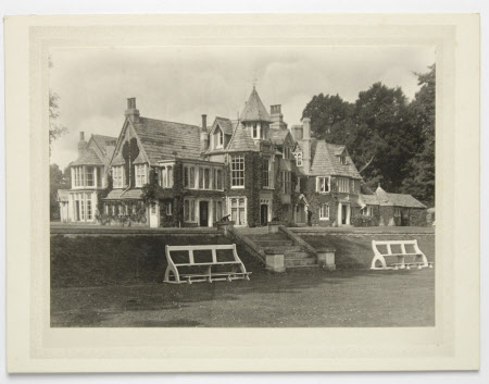 View of south front of Studland Manor, Dorset, with white garden benches flanking the terrace steps
