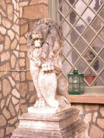 Seated Lion holding Heraldic Shield