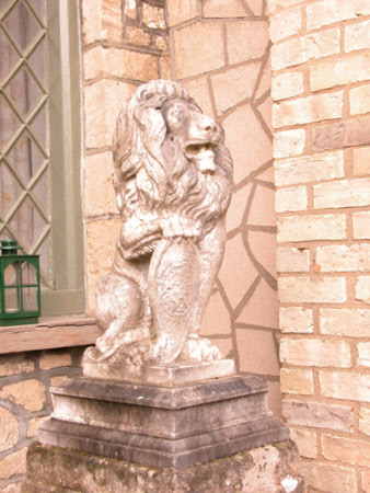 Seated Lion holding a Heraldic Shield
