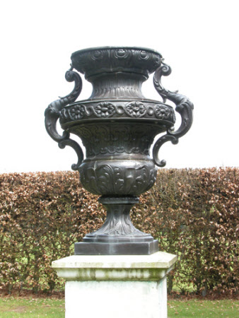 Waisted urns, with repousse leaf mouldings, guilloche and strapwork, with scrolled handles