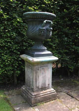 An Urn, the bowl cast with astragals, and handles resting on male masks and oak leaf rim