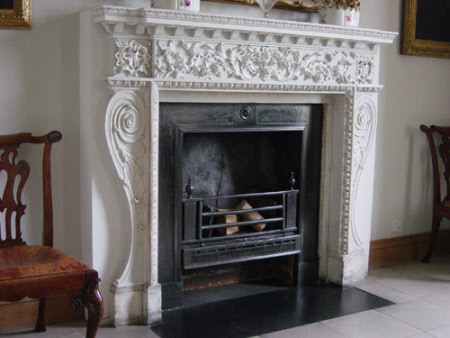 Chimneypiece: white-painted carved wood frieze over white marble uprights with plaster moulding, ...