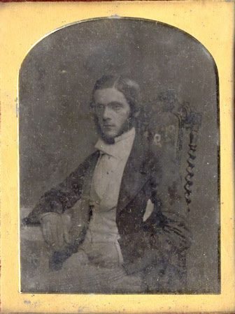 Gentleman seated with his right arm on a table