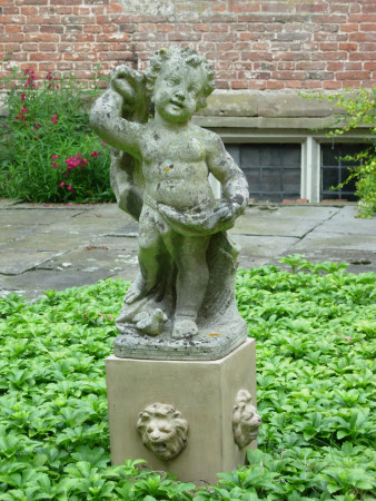 Putto holding a bird on a stone pedestal with four lion masks