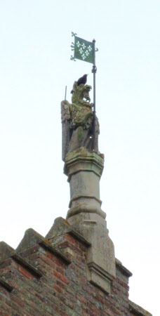 Decorative finial of a falcon holding a pennant.