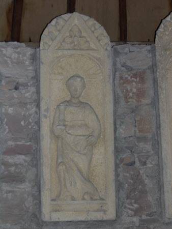 A female saint holding urn in right hand, set into niche.