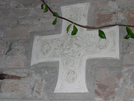 A Celtic Cross depicting Saint carrying a book and quill, decorated with foliage.