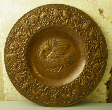 Copper charger with central fantastical bird and floral border