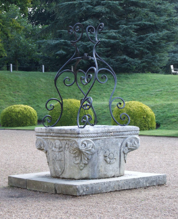A Well-head formed fromed a carved capital with heraldic shields and wrought ironwork