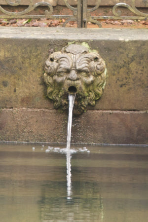 Grotesque mask fountain spout