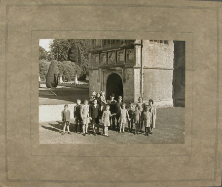 A group of evacuee children accompanied by Mrs. Lee, and William Cole with a pony by the gatehouse ...