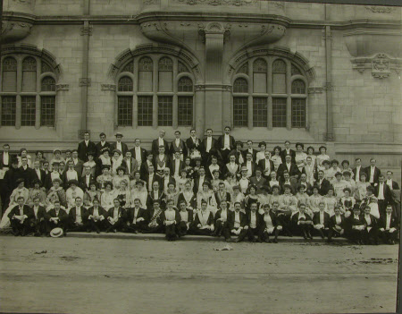 Group of young men and women in evening dress taken outside university building including Captain, ...