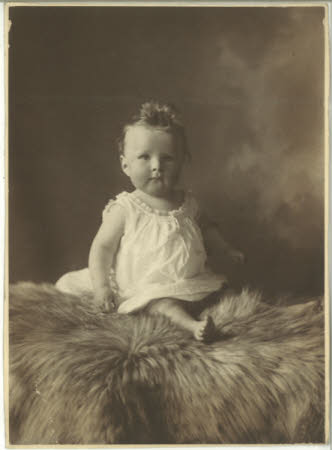 Unknown baby sitting on a fur rug