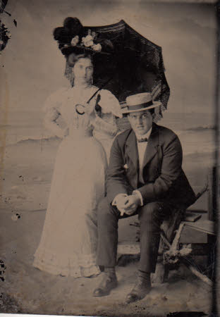 A young man and woman in a studio set to look like a beach.