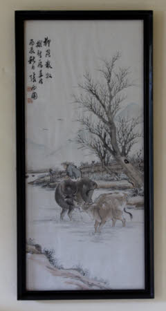 Two water buffalos with a man seated on one under a tree.