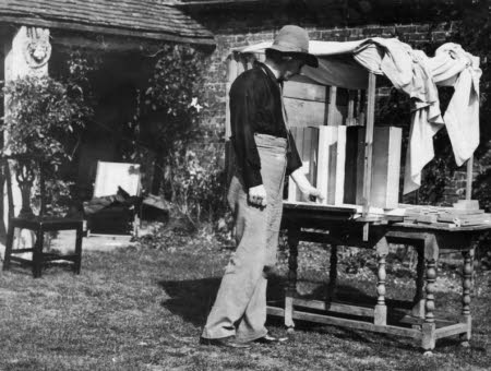 Edward Henry Gordon Craig (1872-1966)  wearing hat, with model stage