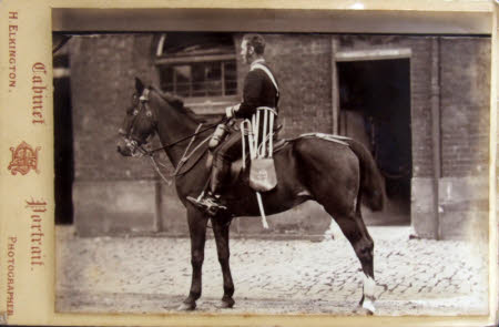 A mounted cavalry messenger posed in front of stables.