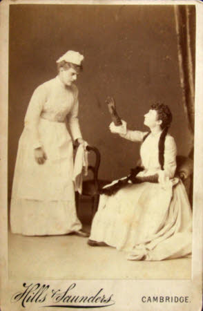 A lady seated gesticulating at a woman, possibly her maid servant.