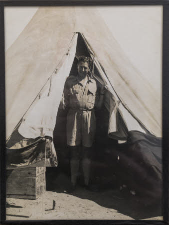 Richard Thomas Wyndham Ketton-Cremer (1909-1941) in uniform standing in front of a tent.