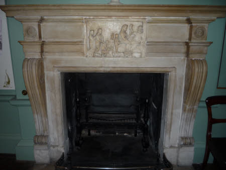 A fireplace with antique sepulchral relief and lekythos