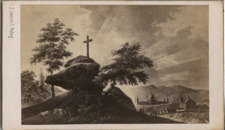 A photograph of an artwork depicting a cross situated atop a rock