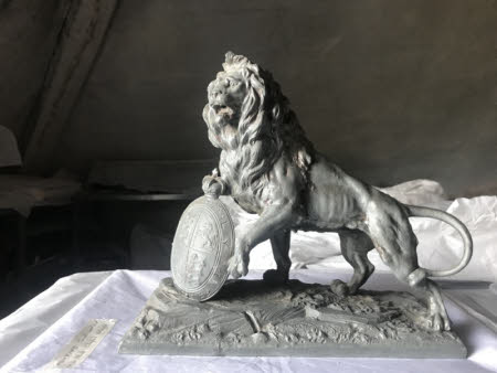 Statant lion supporting a royal coat of arms