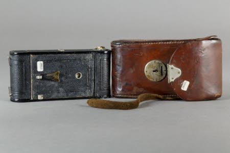A Contessa-Nettel Cocarette folding rollfilm camera in brown leather case.