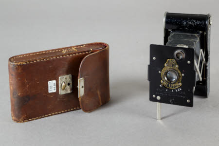 Kodak Vest Pocket Autographic folding rollfilm camera with brown leather case.