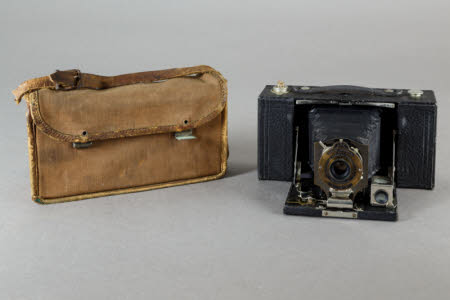 A Kodak No.2 folding pocket Brownie Model B rollfilm camera in a canvas bag with leather strap.