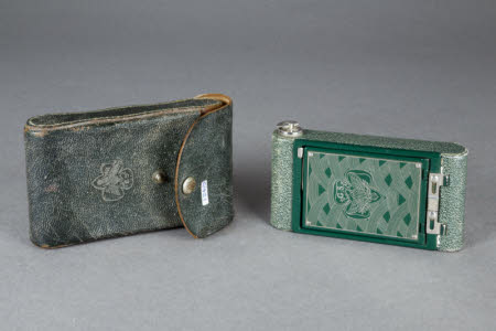 A Kodak Girl Scout folding roll-film camera with green leather case.