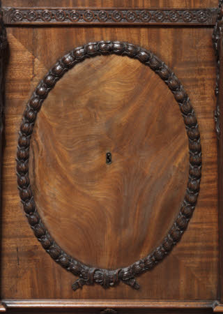 Detail of the applied oval of carved husks framing finely-figured veneers and a brass-lined keyhole to the door of one of the pedestals to the library table © National Trust Images / John Hammond